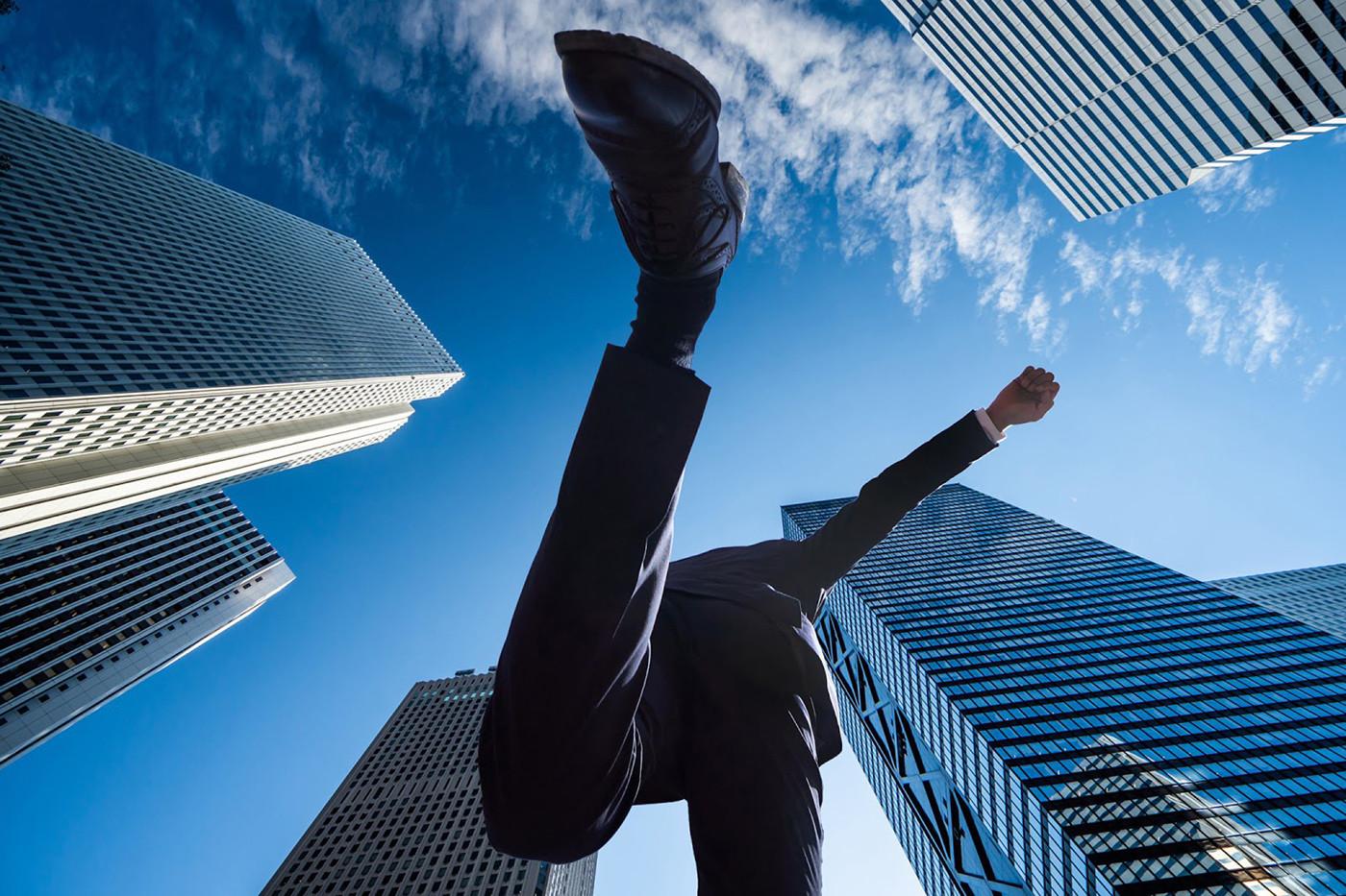 ビル街でスーツを着た男性がジャンプしている様子を下から写したイメージ